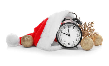 Alarm clock with Santa hat and festive decor on white background. Christmas countdown
