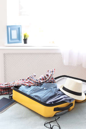 Open suitcase with packed clothes on bed