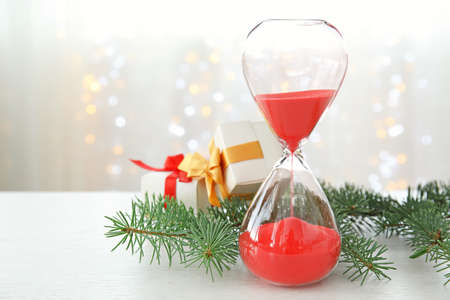 Hourglass with gifts and decor on table. Christmas countdown