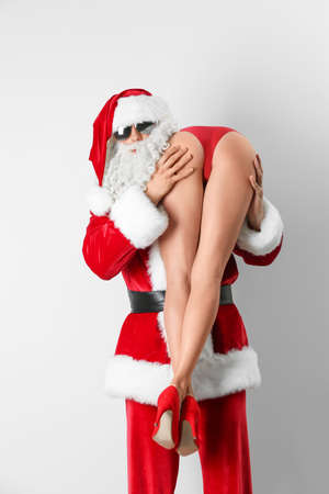 Young Santa Claus holding sexy naked woman on white background