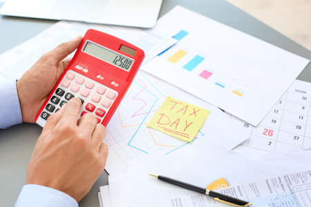 Tax accountant working with calculator at table