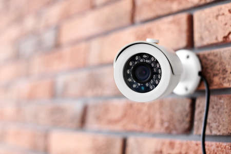 Modern security CCTV camera on brick wall Banque d'images
