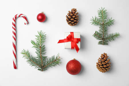 Composition with Christmas tree branches, festive decor and gift box on white background