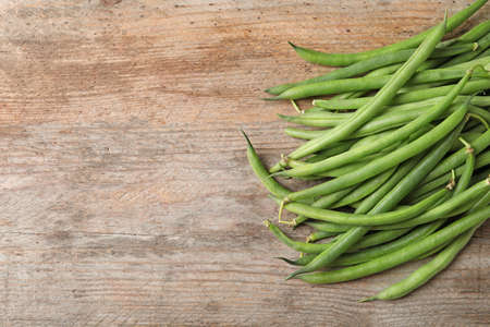 Fresh green French beans on wooden table Stock Photo
