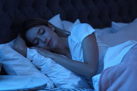 Mujer joven durmiendo en la cama por la noche. Tiempo de sueño Foto de archivo