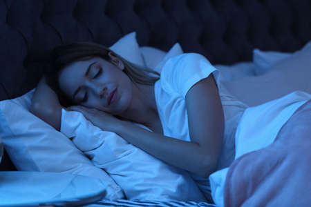Young woman sleeping in bed at night. Sleeping time 免版税图像