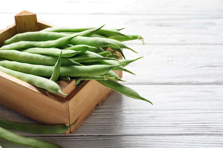 Wooden crate with fresh green beans on table 免版税图像 - 106415721