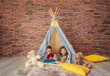Verspielte kleine Kinder im handgemachten Zelt drinnen