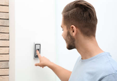 Young man pressing fingerprint scanner on alarm system indoors Archivio Fotografico