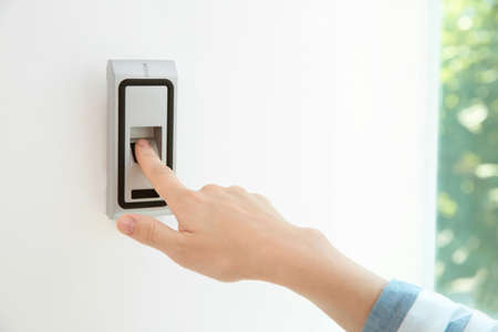 Young woman pressing fingerprint scanner on alarm system indoors