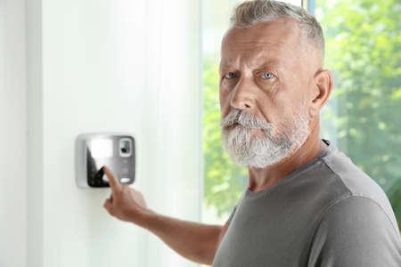 Hombre maduro, ingresando el código en el teclado del sistema de alarma en el interior