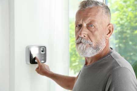 Mature man entering code on alarm system keypad indoors 写真素材