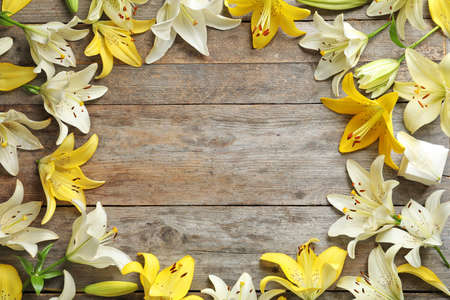 Flat lay composition with lily flowers on wooden background