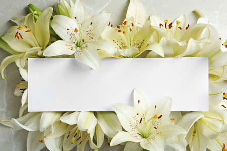 Beautiful lily flowers and blank card, top view Stock Photo - 106205400