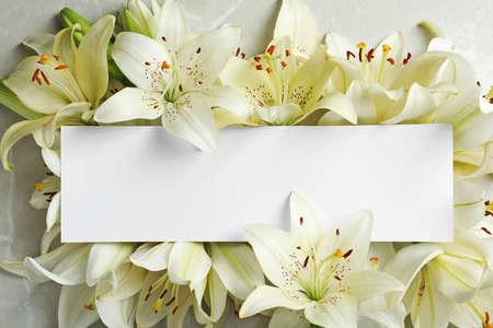 Mooie leliebloemen en lege kaart, bovenaanzicht