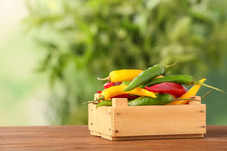 Crate with chili peppers on table against blurred background