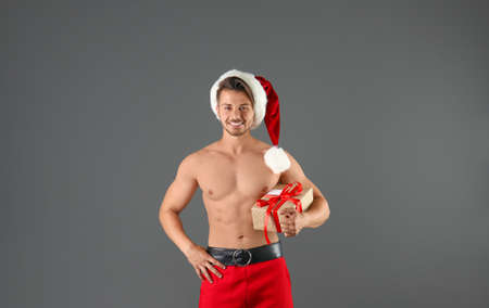 Shirtless sexy young Santa Claus with gift on color background Banco de Imagens