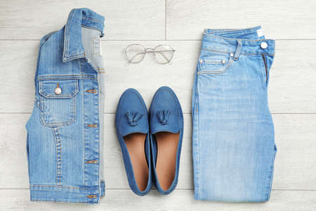 Flat lay composition with blue jeans, jacket and shoes on wooden background