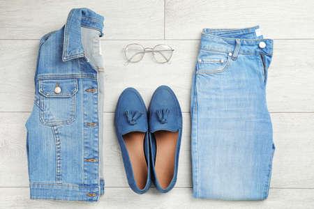Flache Komposition mit Blue Jeans, Jacke und Schuhen auf hölzernem Hintergrund Standard-Bild