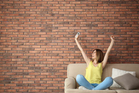 Happy woman with air conditioner remote at home