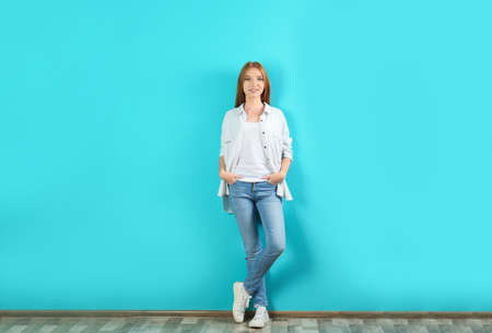 Young woman in stylish jeans near color wall Stock Photo