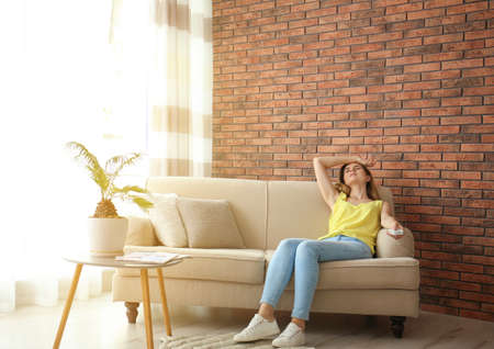 Woman with air conditioner remote suffering from heat at home