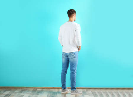 Young man in stylish jeans near color wall