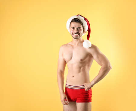 Shirtless young Santa Claus with sexy body on color background