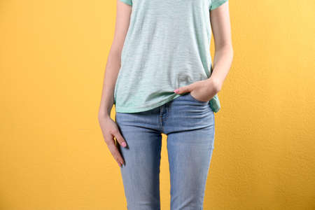 Young woman in stylish jeans on color background Stock Photo