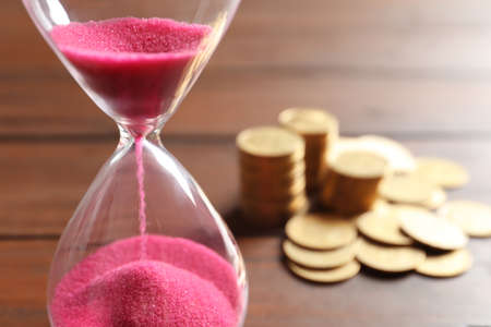 Hourglass with flowing sand on table, closeup. Time management Banque d'images