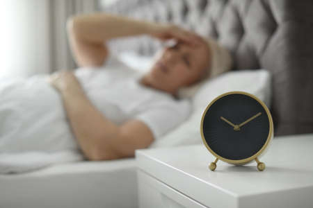 Alarm clock on nightstand with mature woman suffering from headache on background
