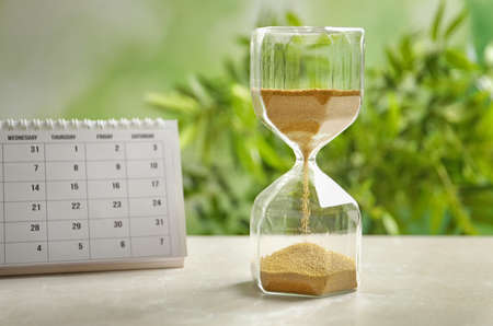 Hourglass and calendar on table against blurred background. Time management
