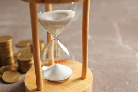 Hourglass with flowing sand and coins on table. Time management