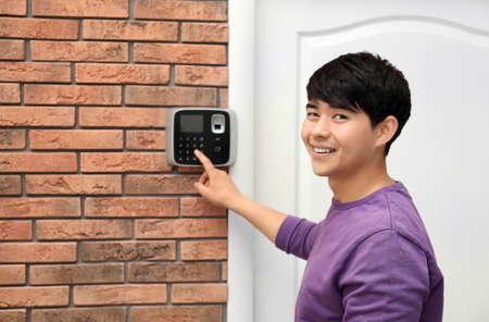 Young man entering code on alarm system keypad indoors