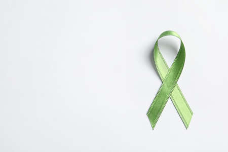 Green ribbon on white background, top view. Cancer awareness