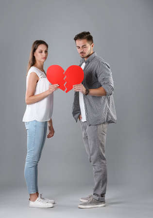 Young couple with torn paper heart on grey background. Relationship problems Stock Photo