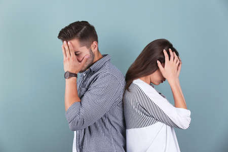 Upset young couple on color background. Relationship problems
