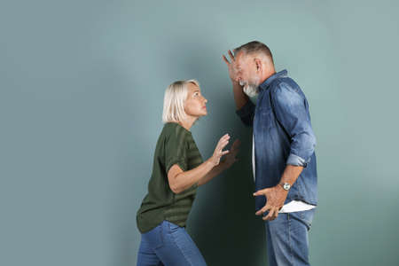 Mature couple having argument on color background. Relationship problems