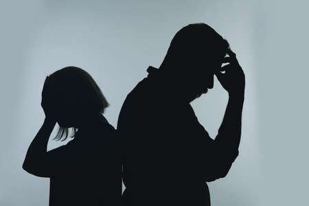 Silhouette of couple having argument on color background. Relationship problems Фото со стока