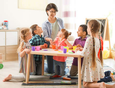 Young woman playing with little children indoors