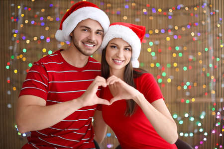 Young couple in Santa hats putting hands in shape of heart on blurred lights background. Christmas celebration Stock Photo