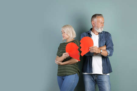 Mature couple with torn paper heart on color background. Relationship problems
