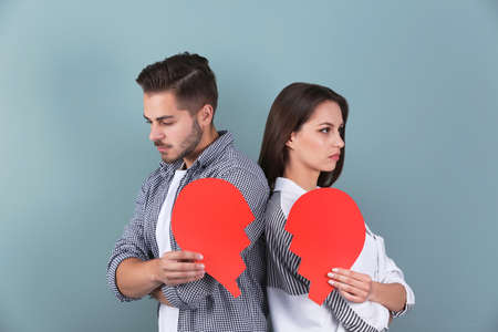 Young couple with torn paper heart on color background. Relationship problems