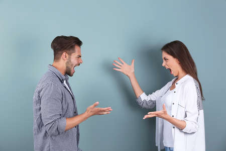 Young couple having argument on color background. Relationship problems