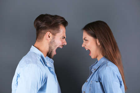 Young couple having argument on grey background. Relationship problems