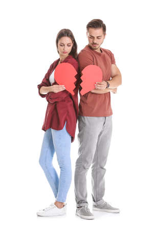 Young couple with torn paper heart on white background. Relationship problems