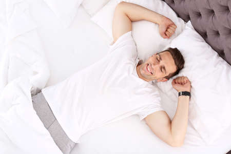 Young man after sleeping in bed at home, top view
