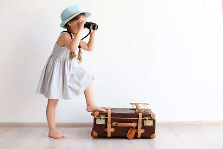 Adorable little child playing traveler with suitcase indoors Imagens