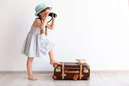 Schattige kleine kind spelende reiziger met koffer binnenshuis