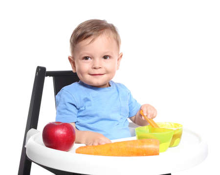 Adorable little child having breakfast in highchair against white background. Healthy baby food Archivio Fotografico